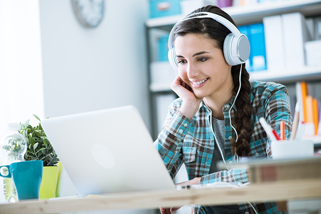 Teenage smiling girl using a laptop and wearing headphones, technology and leisure concept